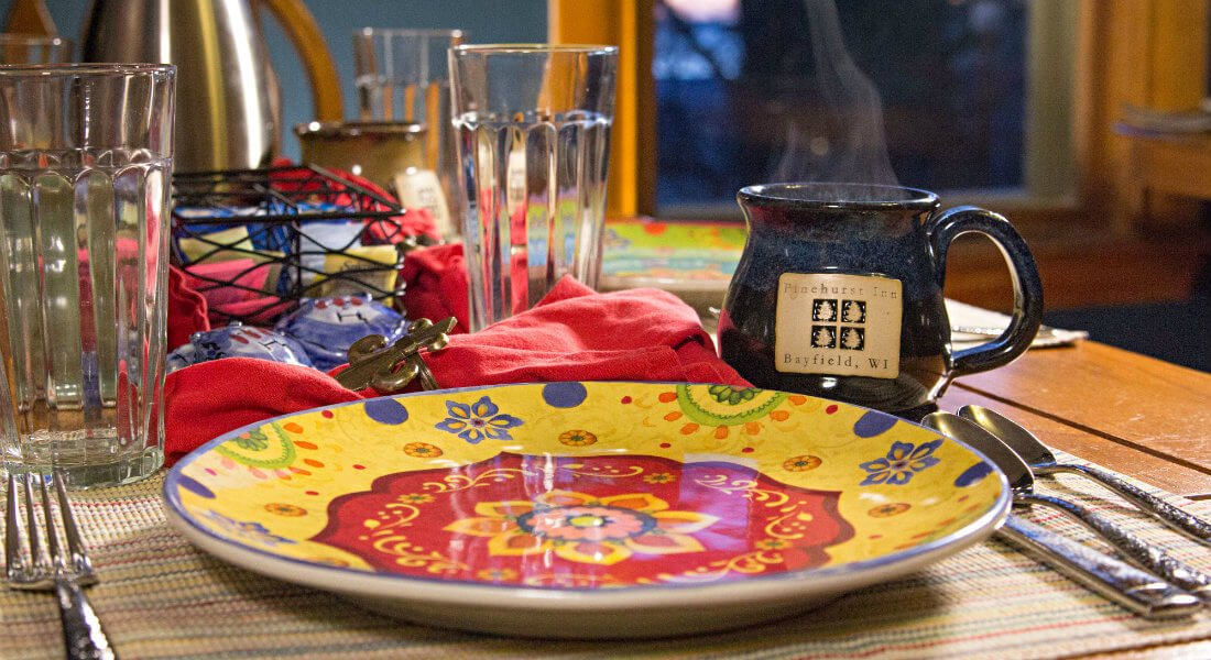 Close up view of table set with colorful plate, coffee mug and glasses