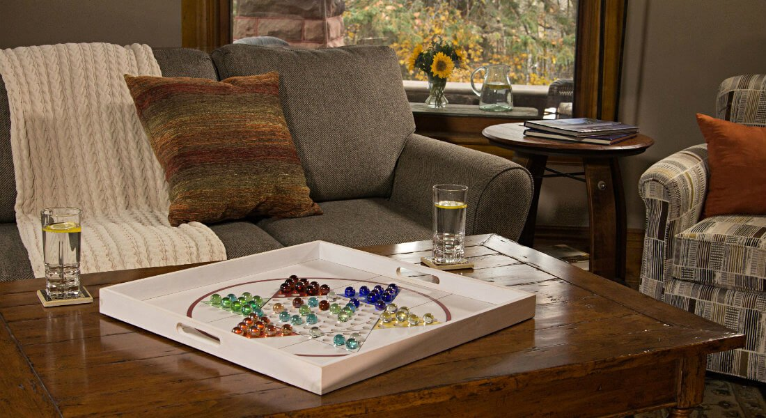 Wood coffee table topped with Chinese checkers, and an upholstered sofa and chair flanking a round table