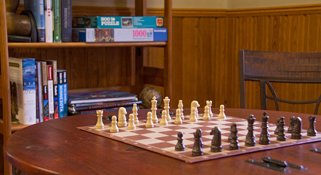Chess game on a wood table with a shelf in the background filled with puzzles and books