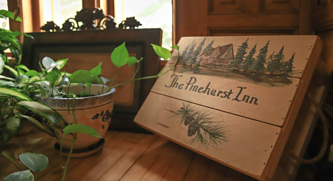 Wood table topped with a green plant and a wood sign that says The Pinehurst Inn