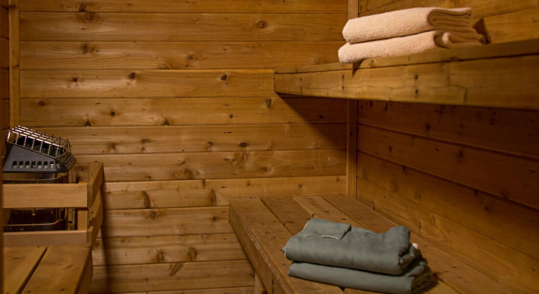 Wood sauna with shelves, benches and towels