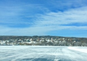Frozen Ice road with distant view of winter scene small town, wispy clouds.