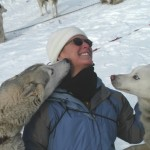 woman in blue jacket and white cap between two huskie dogs licking her face