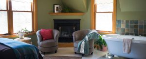 guest room with green walls, corner fireplace, large clawfoot tub and two gray upholstered chairs