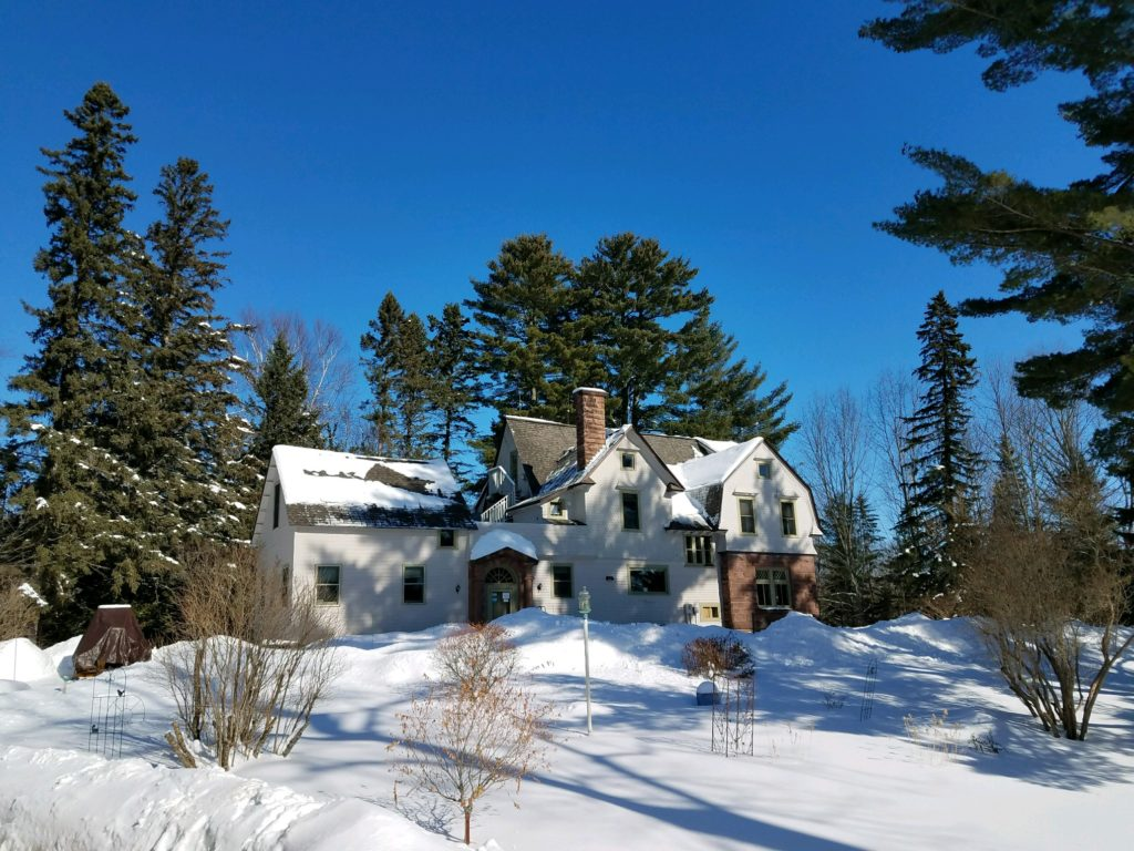 Main House on snow covered lot with towering green pine trees and deep blue sky