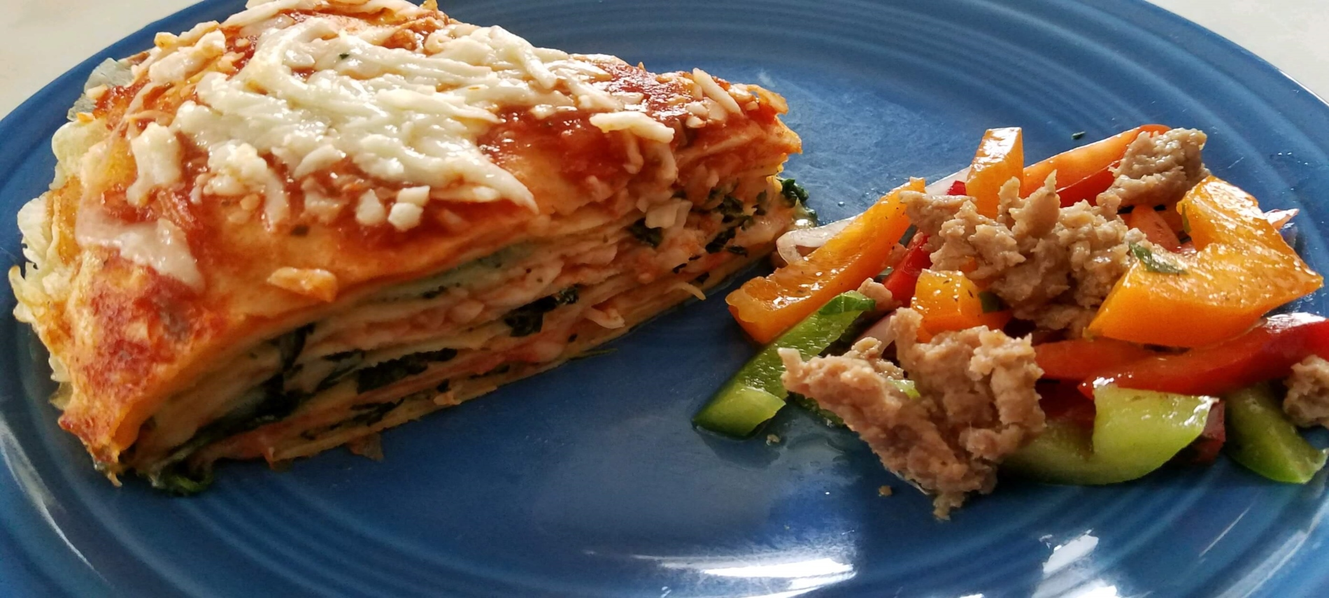 Triangle piece of lasagna on blue plate with red, orange and green pepper and sausage salad