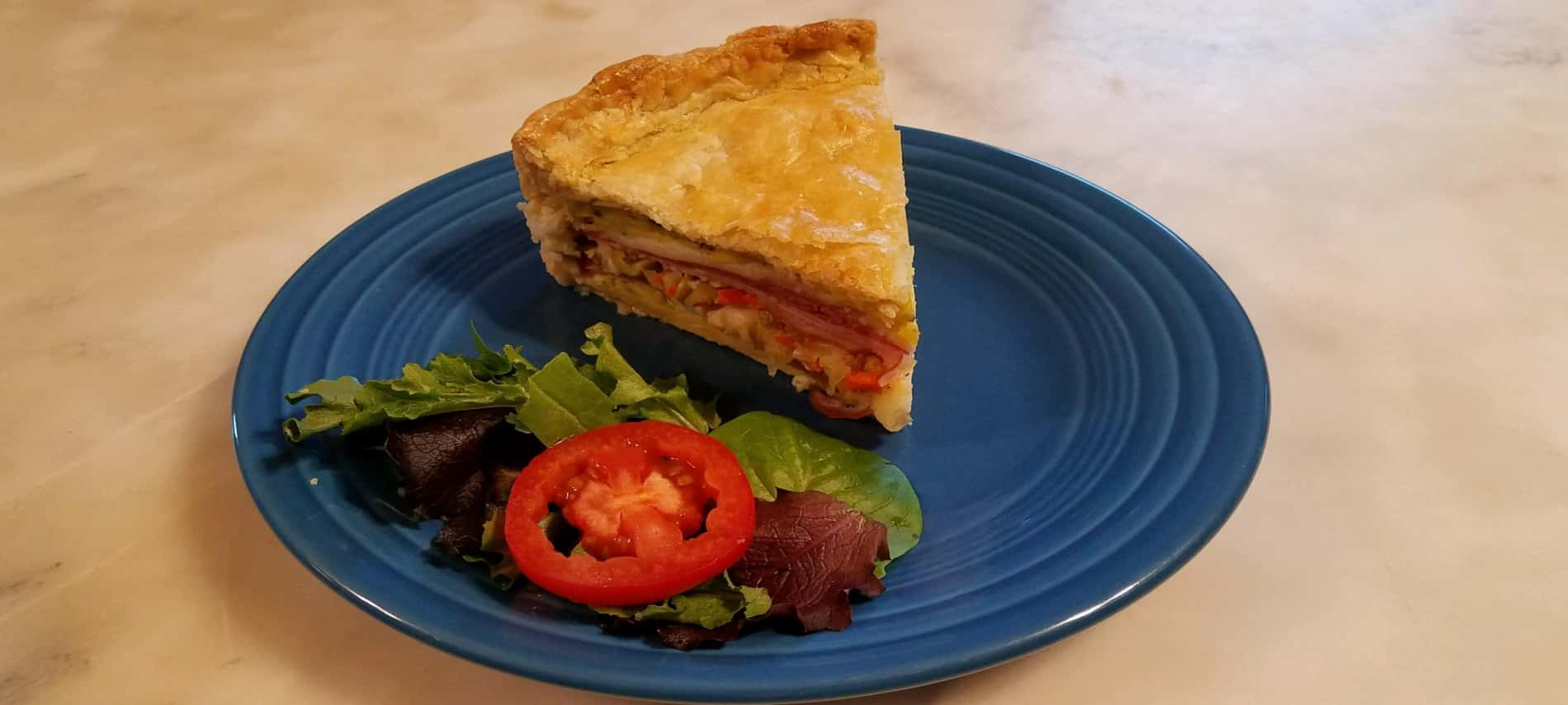 layers of ham, salami, cheese and olive salad in pie crust on blue plate with greens and tomato slice