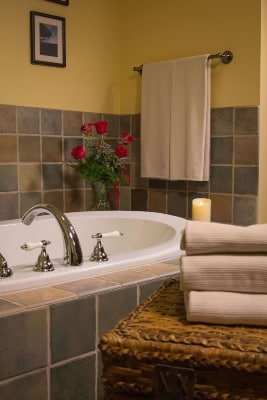 large white jetted tub with green tile surround and stack of tan towels and a vase with red roses
