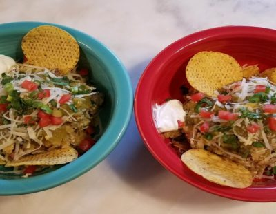 red and turquoise bowls with egg and pork mixture in center with tortilla chips, sour cream, dice tomatoes and green onions