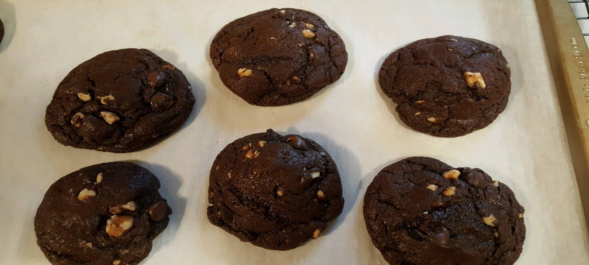 six chocolate chunky cookies on white parchment paper on cookie sheet