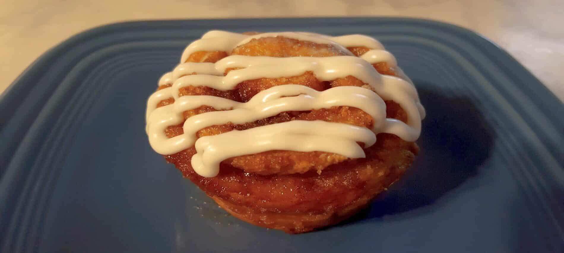 light brown muffin with cinnamon swirl, topped with cream cheese glaze on blue plate
