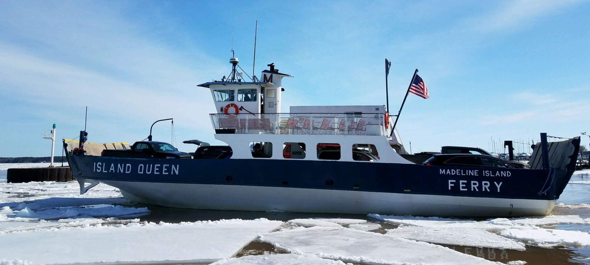 Madeline Island Ferry breaking through ice on a clear day with blue sky
