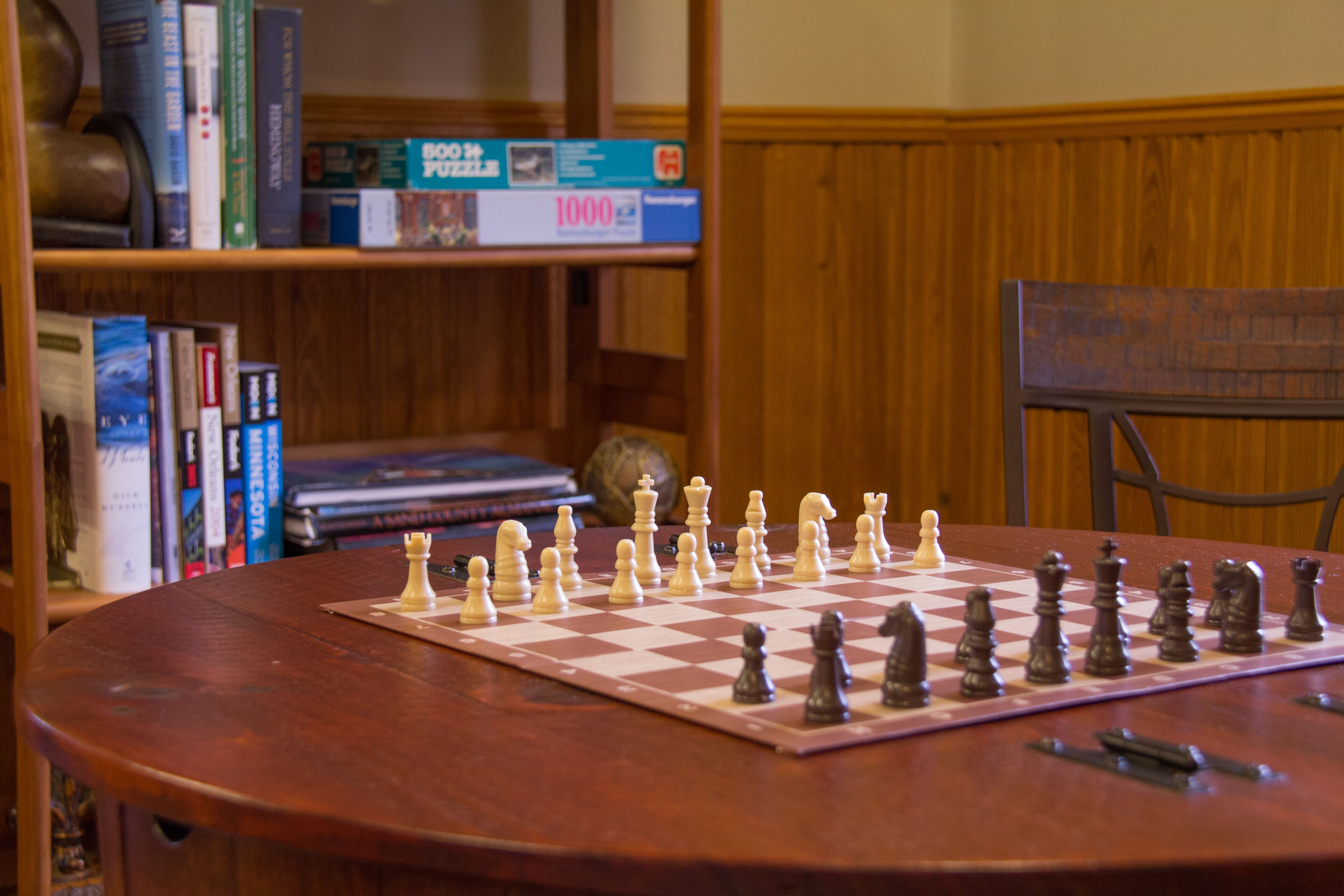 chess set on wood table with chair and shelves with books and puzzles in background