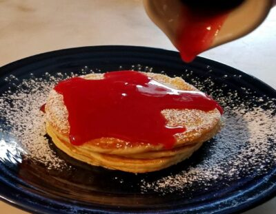 dark blue plate with golden brown pancakes with cranberry syrup poured from pitcher on top of pancakes