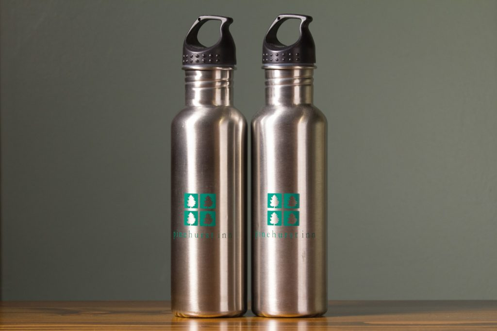 Two stainless steel water bottles with pinehurst inn logo on wood table and green background