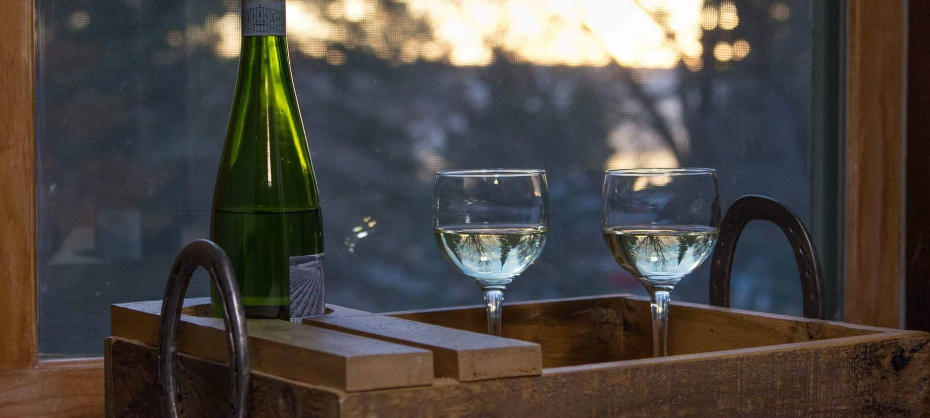 brown wooden tray with wine glasses and wine in front of window overlooking sunrise