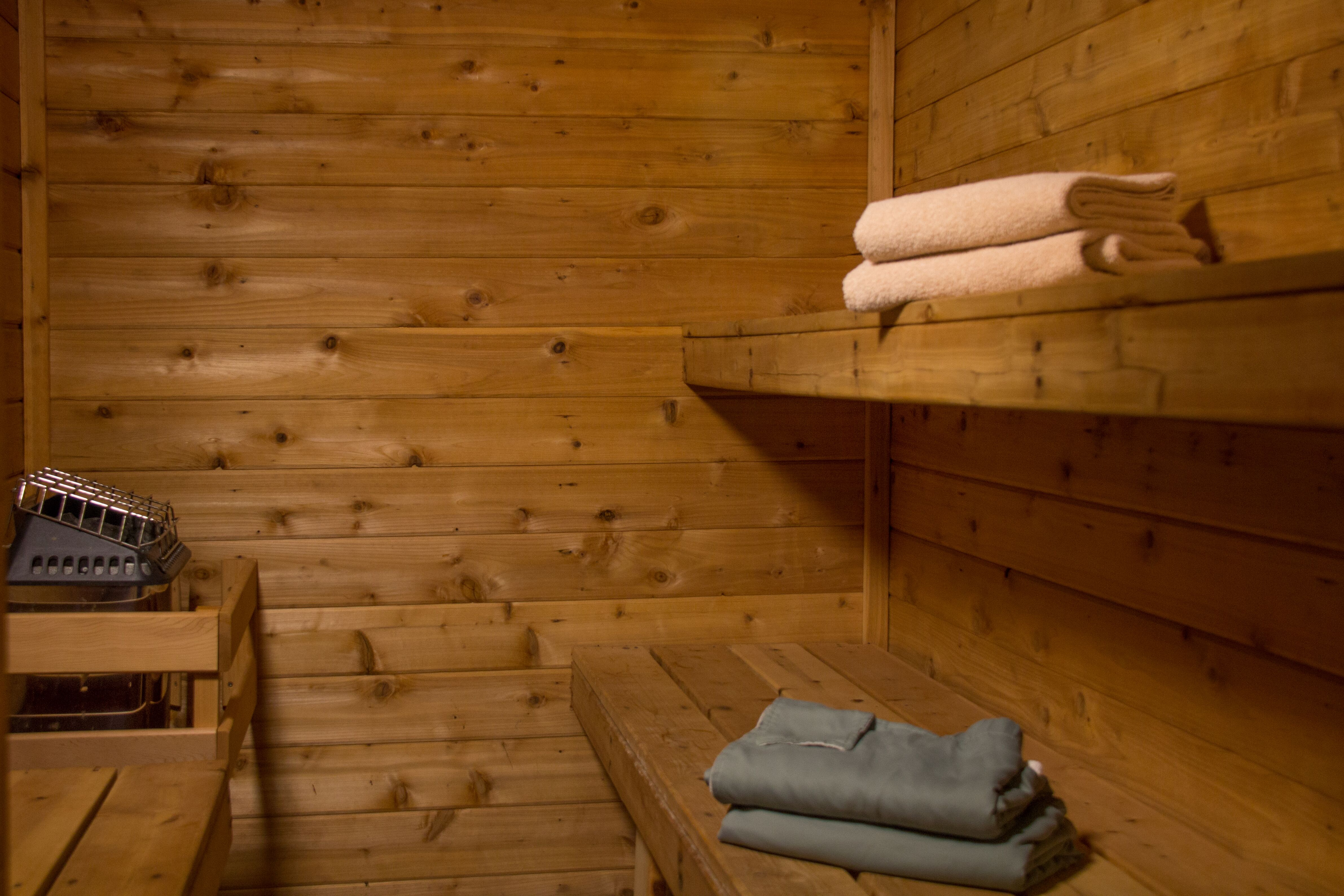 interior of sauna with wood siding, two wood benches with folded blue robes and beige towels