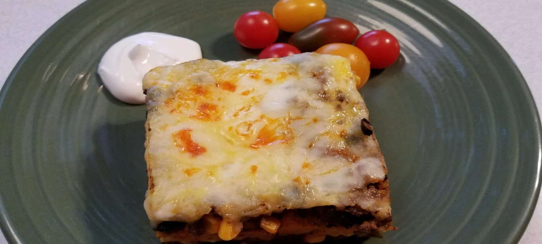 Layered South of the Border Breakfast Lasagna with melted cheese on top, served on a green plate with sour cream and multi colored cherry tomatoes