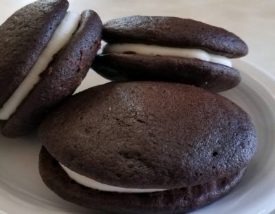 three chocolate with vanilla cream whoopie pies on white plate