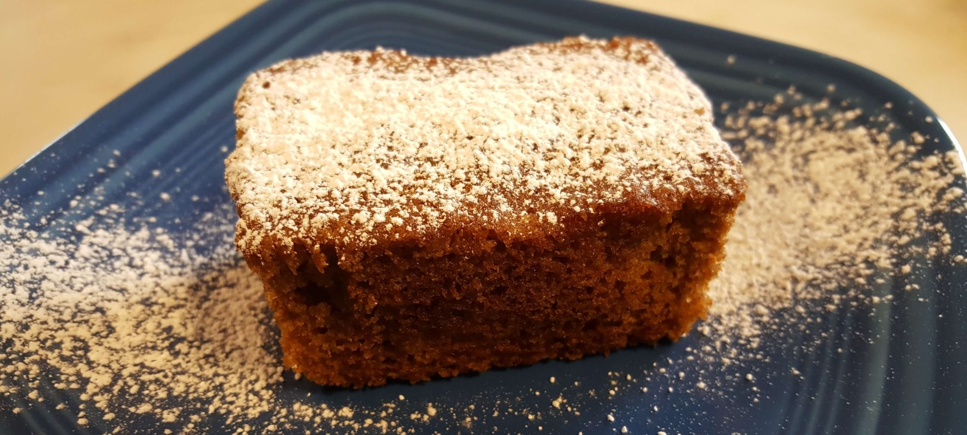 mini loaf shape brown cake sprinkled with powdered sugar on blue plate