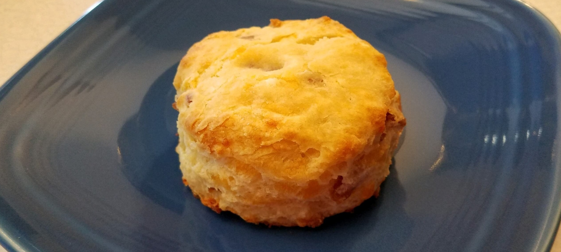 golden bacon cheddar biscuit on a blue plate