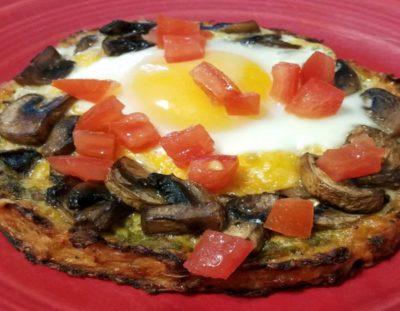 small round pizza with mushrooms, egg and yellow yolk topped with chopped tomatoes on a red plate