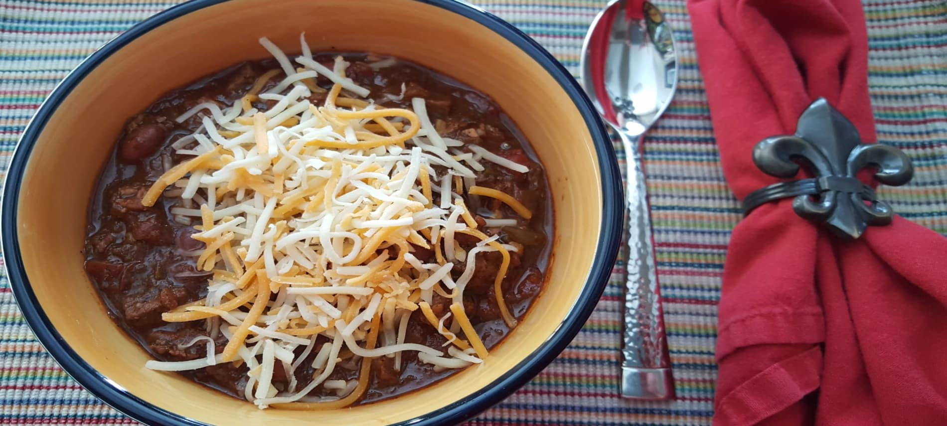 yellow and blue bowl of chili with grated cheddar and jack cheese with spoon and red napkin with fleur de lis napkin holder