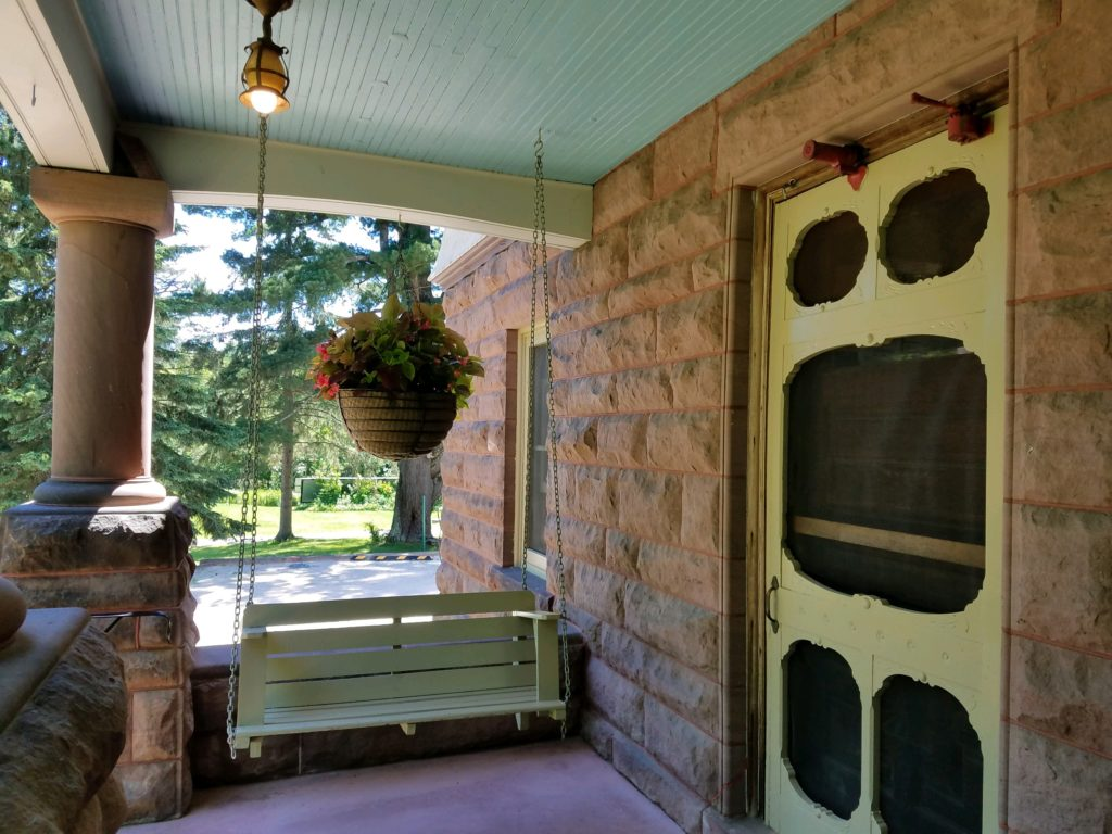 brownston front porch with green antique screen door, porch swing and hanging basket
