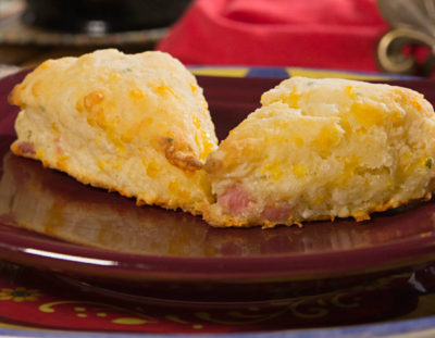 Burgundy ceramic plate on a colorful ceramic charger topped with two ham and cheese scones
