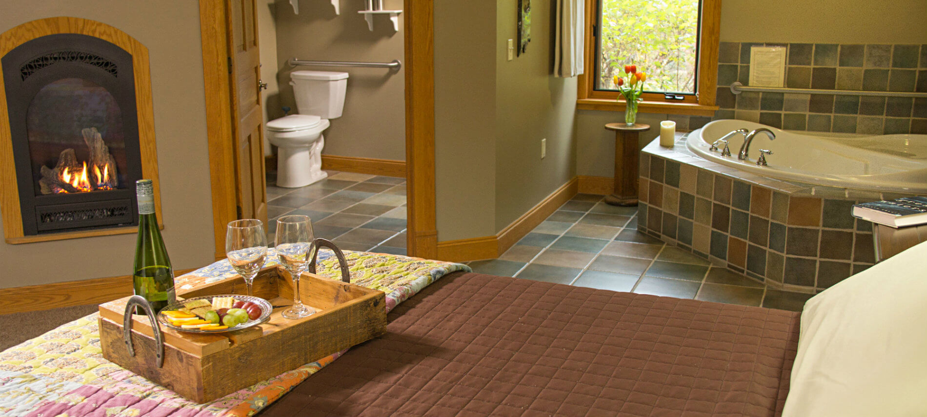 Tan guest room with fireplace, bed topped with tray of wine, cheese, crackers and grapes, and view of corner soaking tub