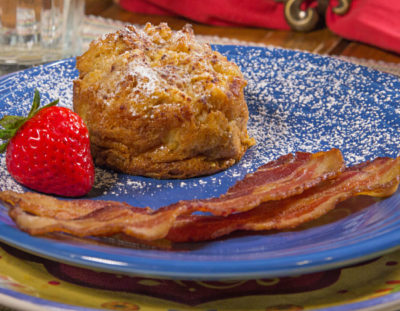 Blue ceramic plate on a colorful charger topped with bacon, red strawberry and golden baked french toast
