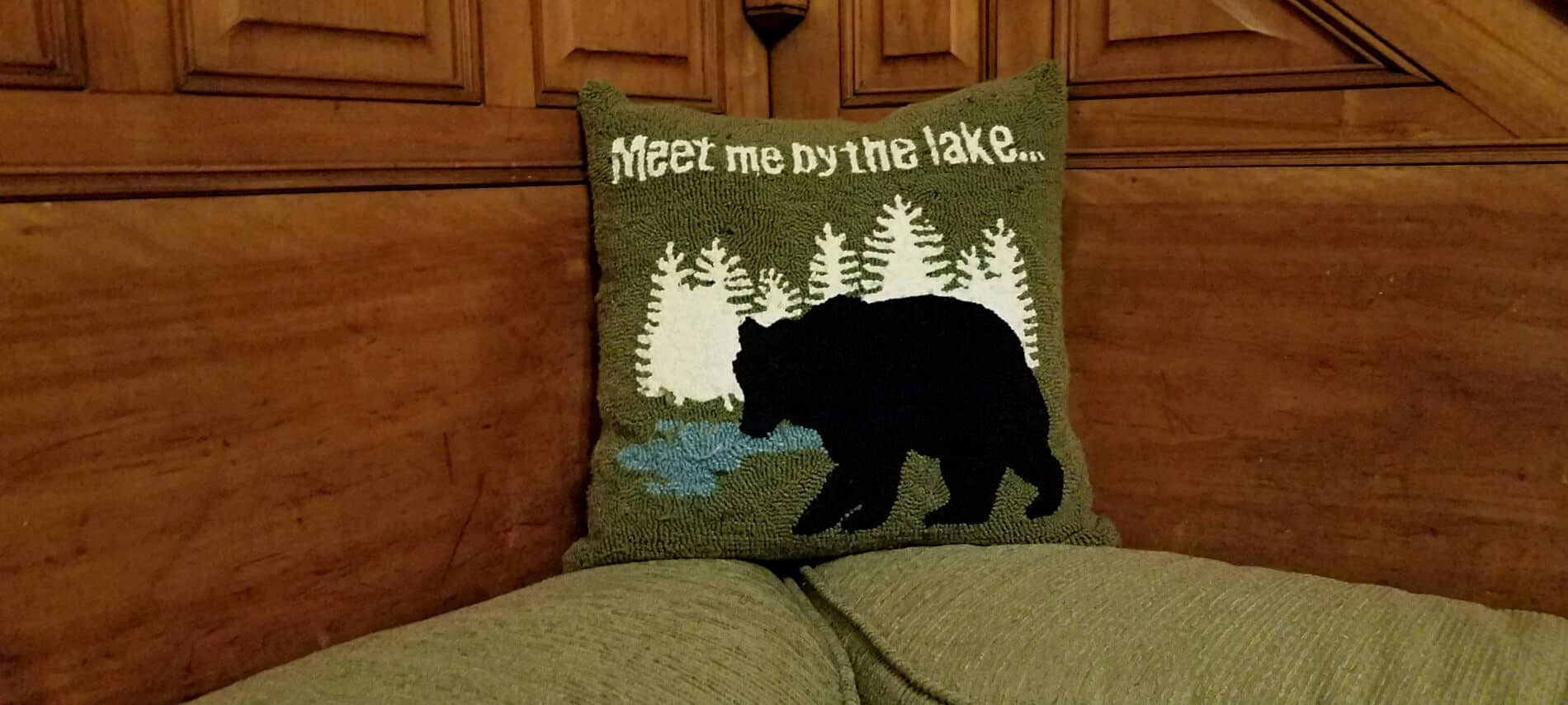 Close up view of green throw pillow that says, Meet me by the lake...