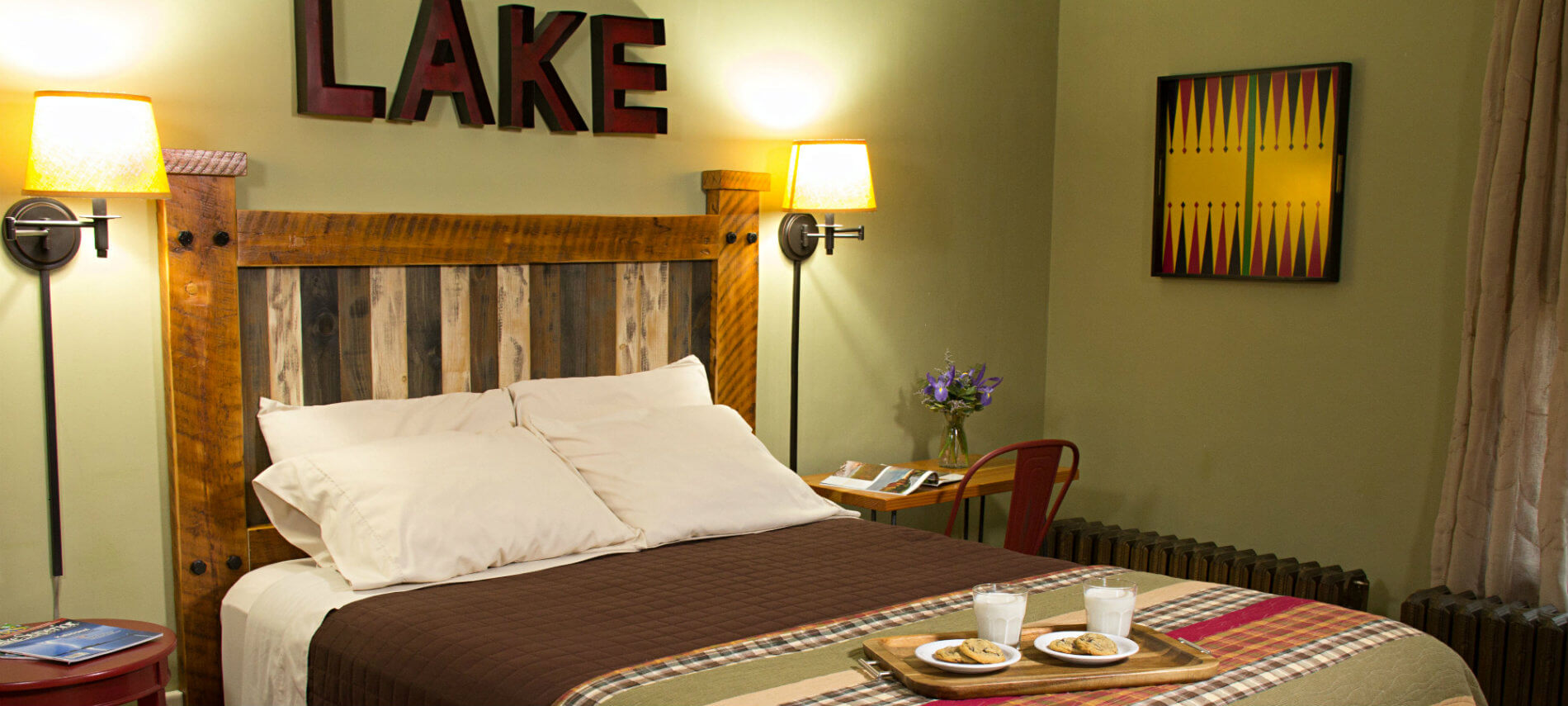 Light green guest room, bed with wood headboard and tray of cookies and milk, nightstands and reading lights