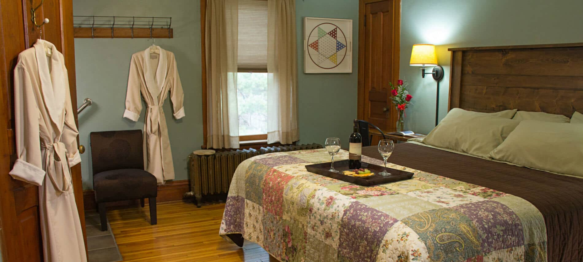 Blue green guest room, wood floors, quilt covered bed with wood headboard and tray of grapes and wine