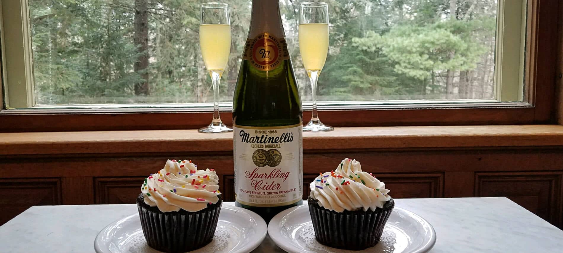Two champagne glasses and bottle of sparkling cider and two cupcakes with sprinkles in front of a window overlooking trees