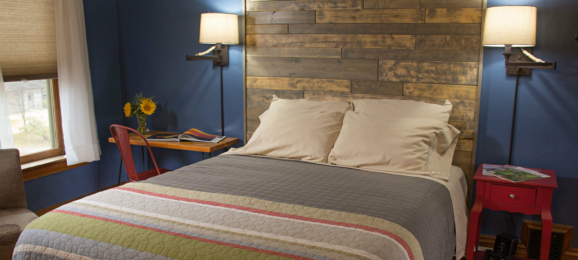 Blue guest room, bed with striped quilt and shiplap headboard, two nightstands and reading lights, and window