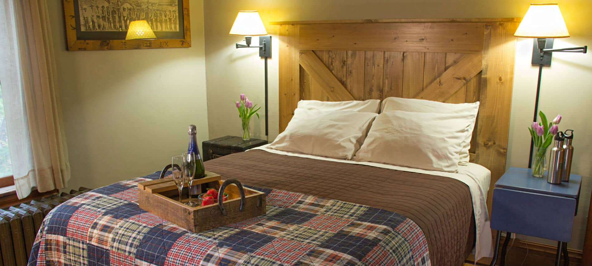 Beige guest room, bed with plaid quilt and rustic wood headboard, tray of strawberries and champagne, nightstands and reading lights