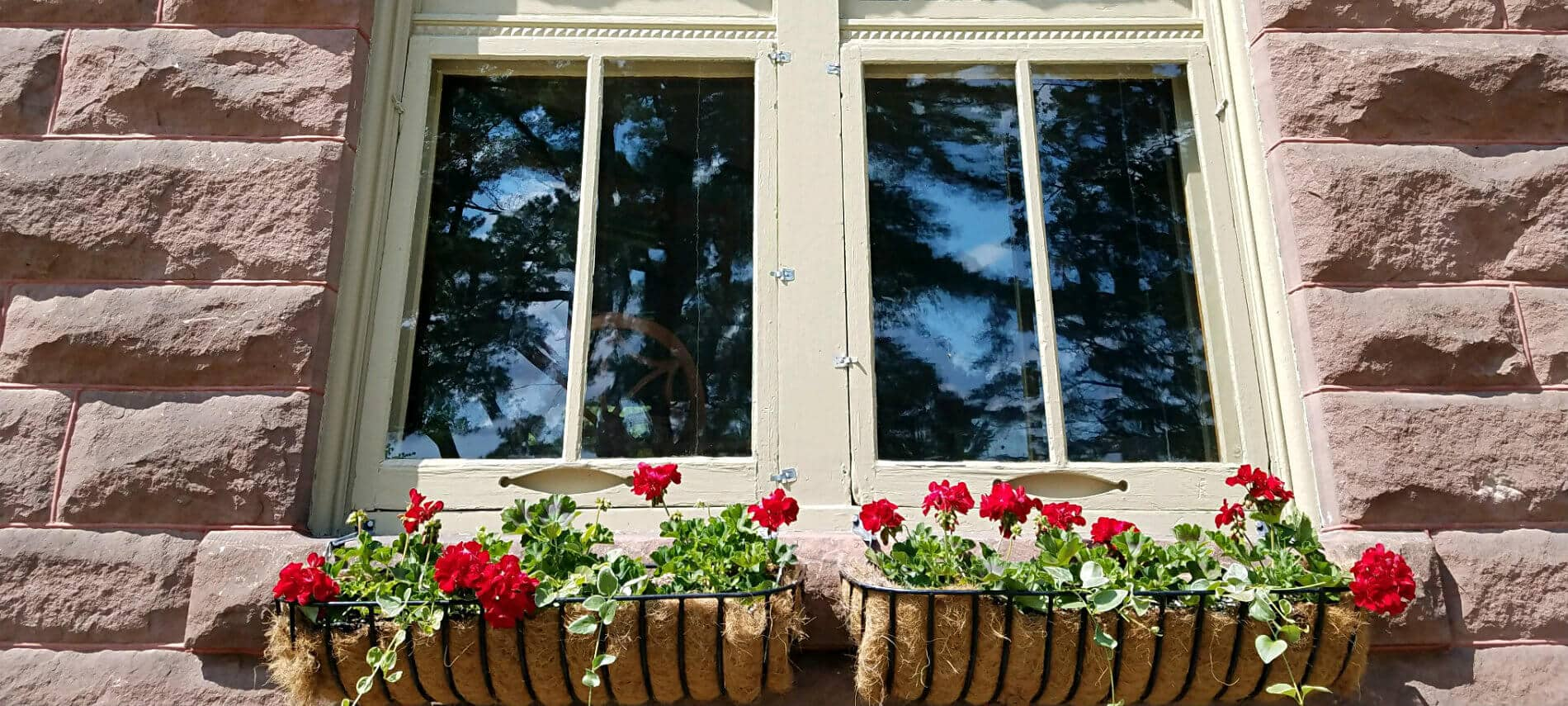 Close up view of exterior window surrounded by reddish stone and two window boxes with bright red flowers