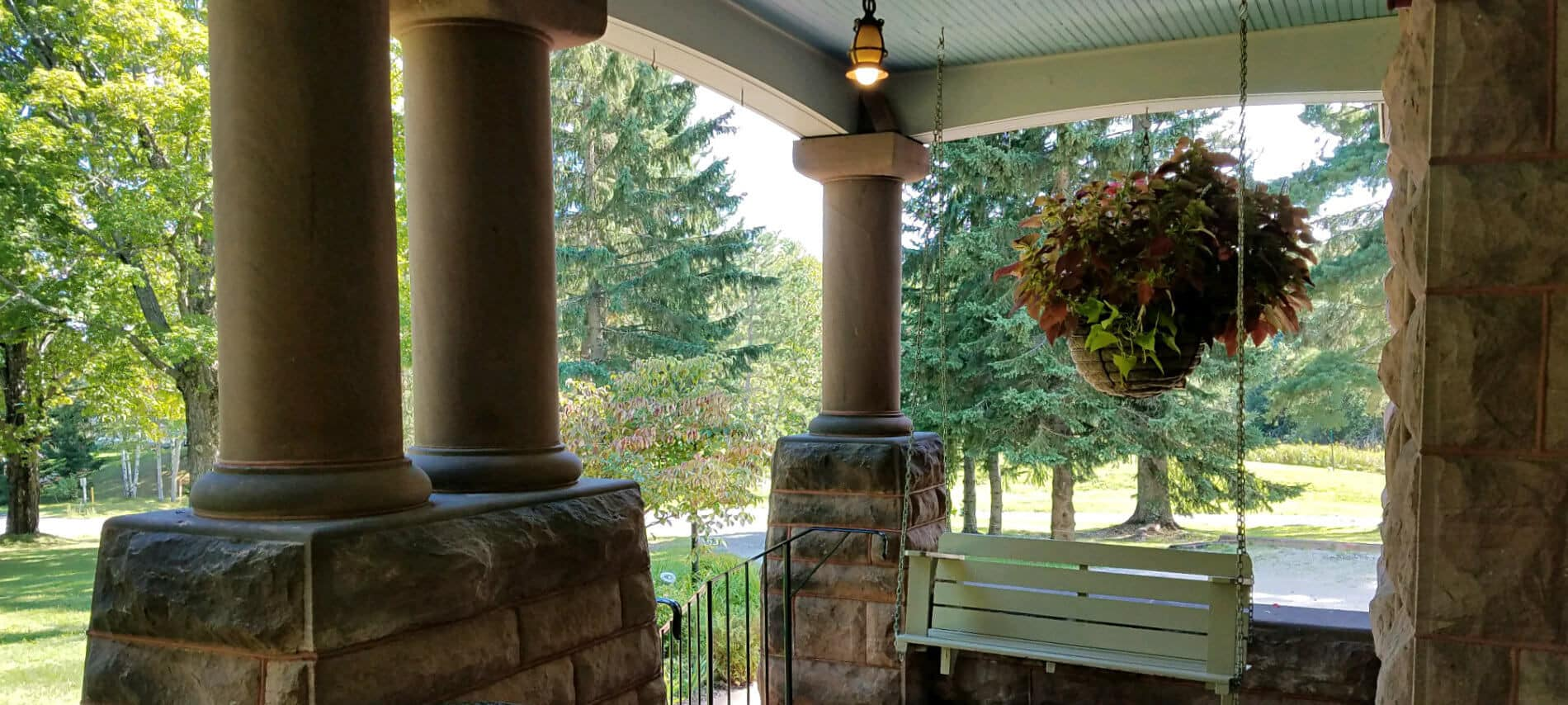 Covered porch with round pillars with stone bases, wooden porch swing, large hanging plant, all surrounded by trees