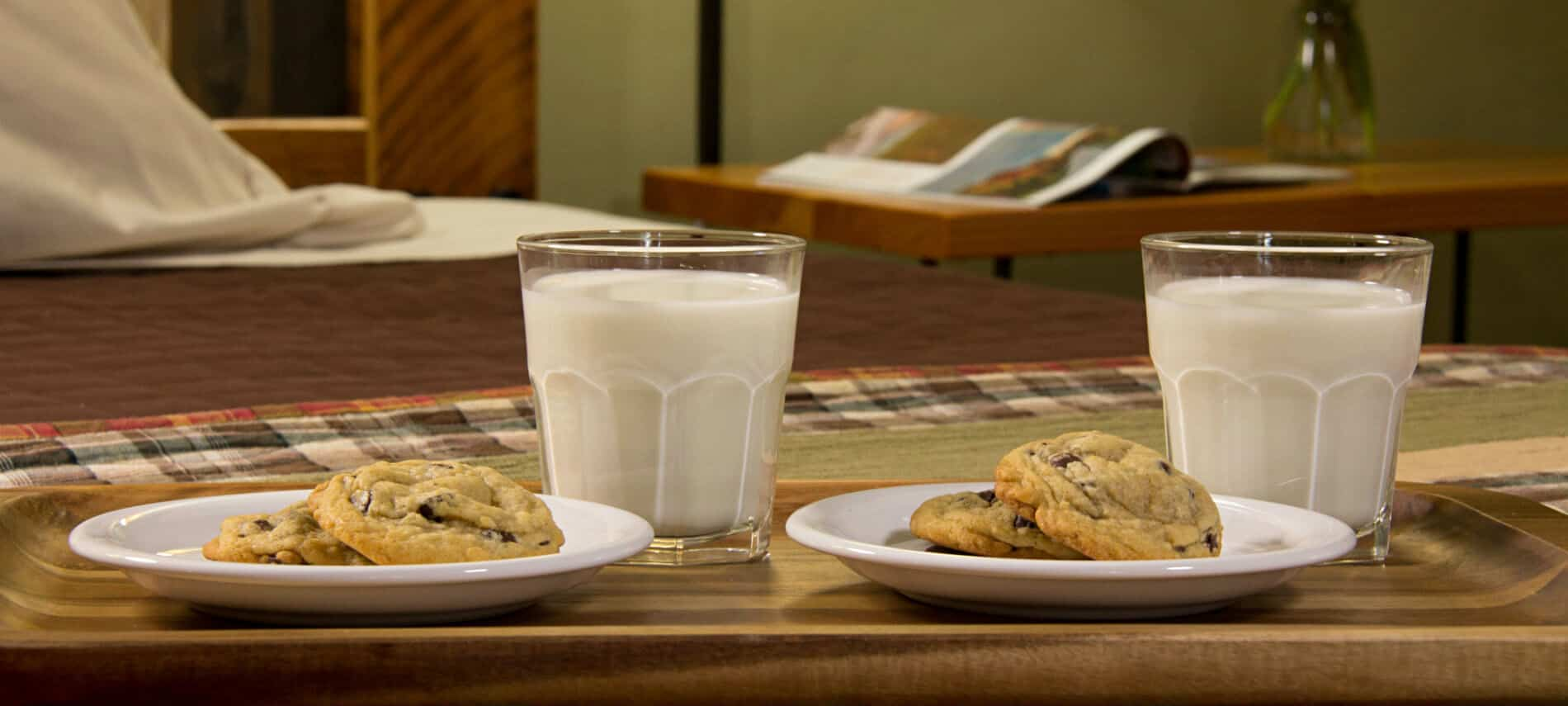 Wood tray topped with two white plates of chocolate chip cookies and two glasses of milk