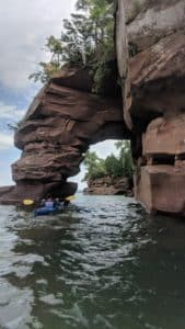 kayaker on lake superior entering brownstone arch with trees in the distance