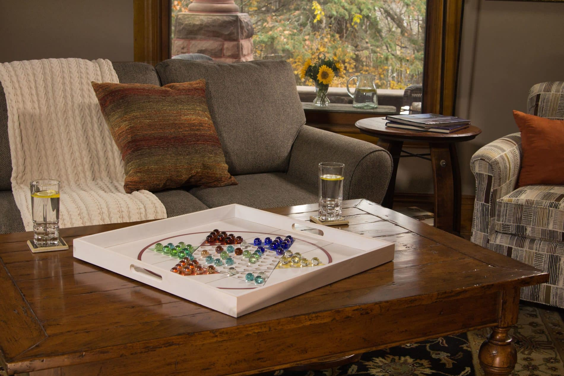 gray couch with multi color throw pillow and wood coffee table with large white chinese checkers board and two glass of water with lemon on top