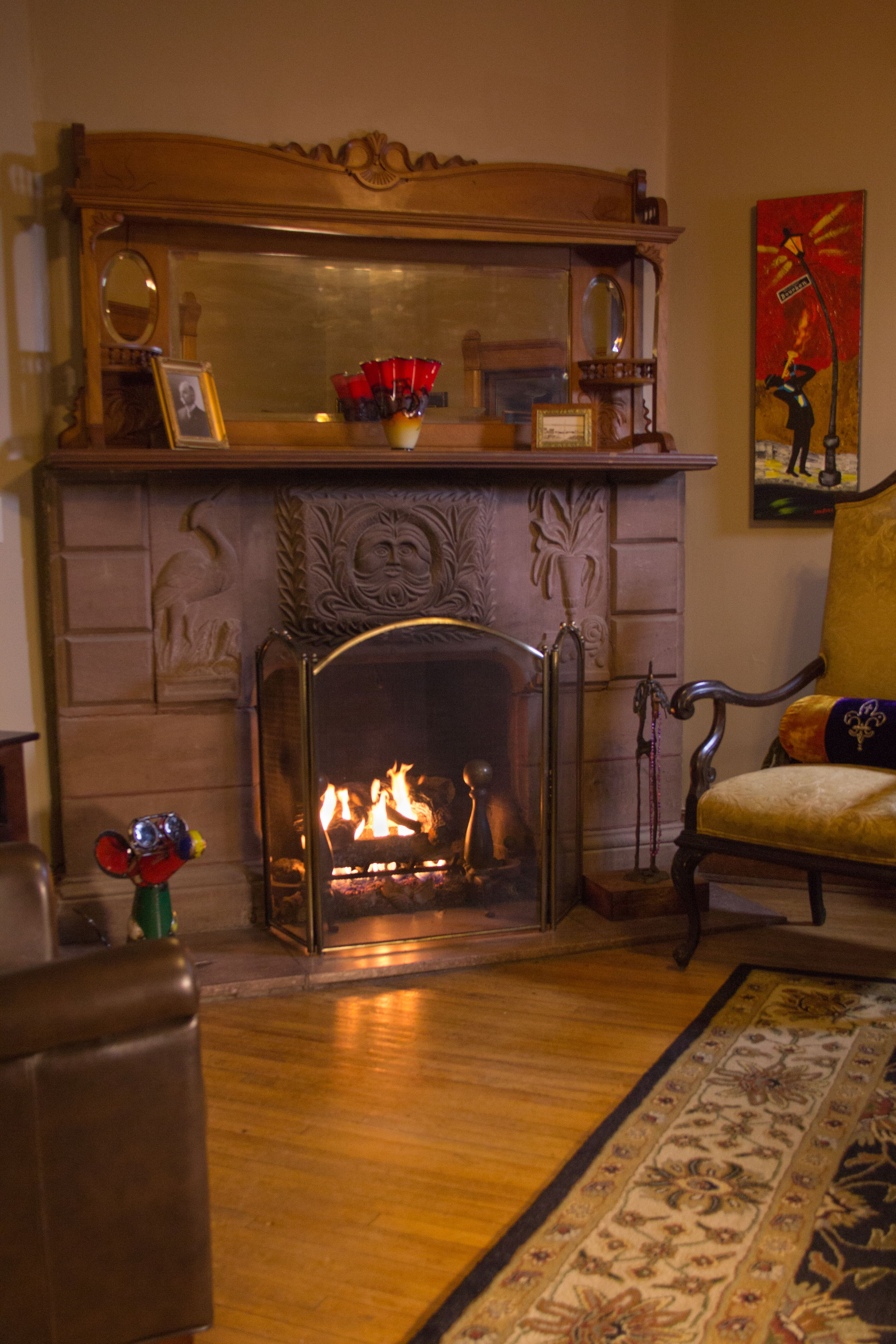 brownstone carved fireplace with roaring fire with mantle and mirror and a gold antique chair next to it