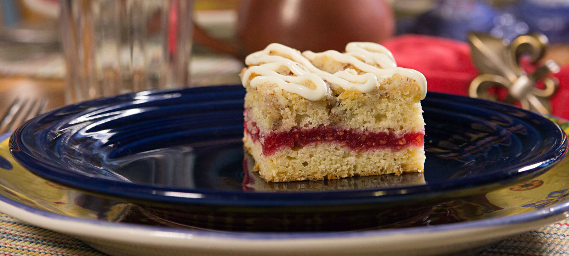 Blue ceramic plate on a colorful ceramic charger topped with a piece of raspberry coffee cake drizzled with icing