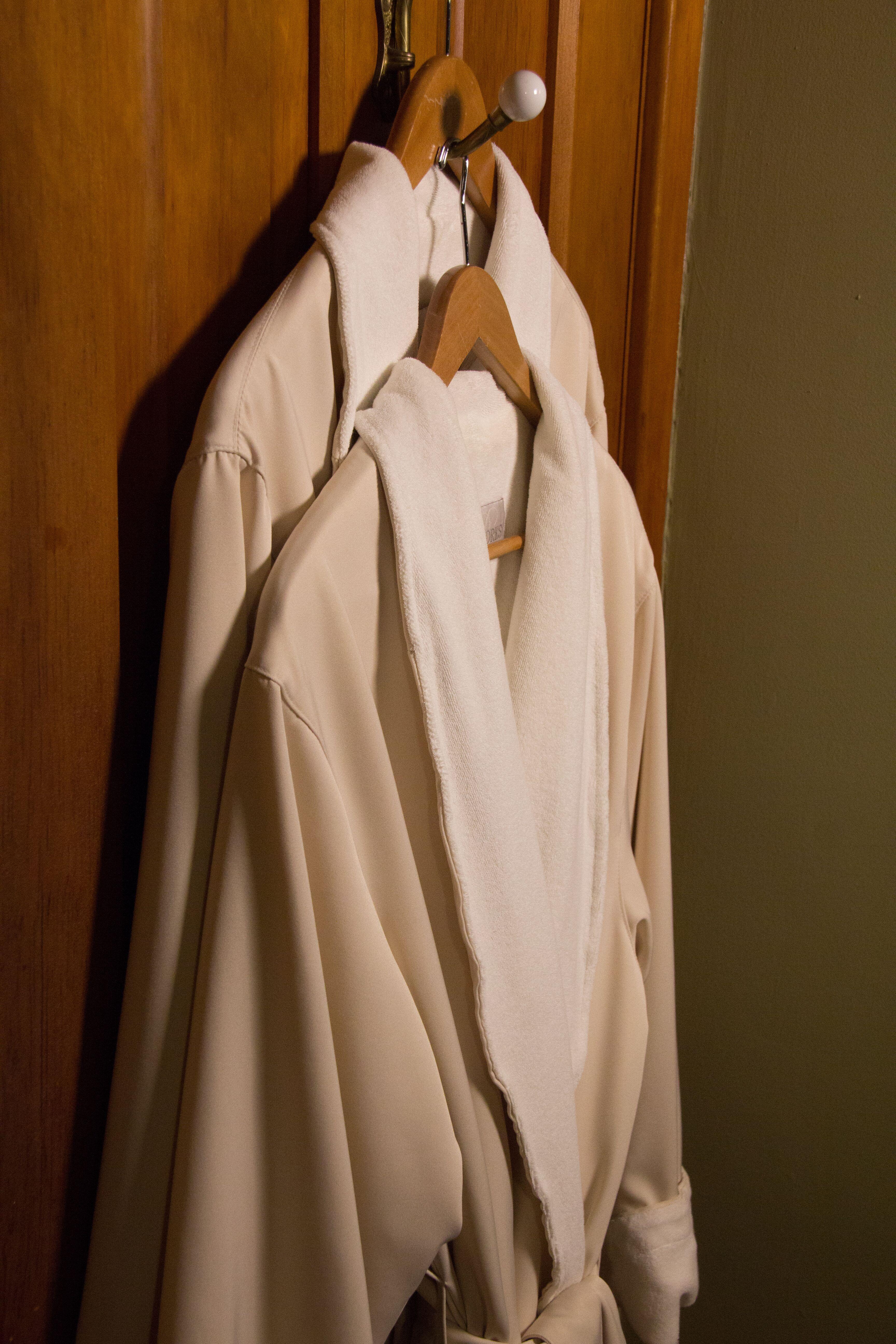 two cream colored robes handing from hook on wooden door