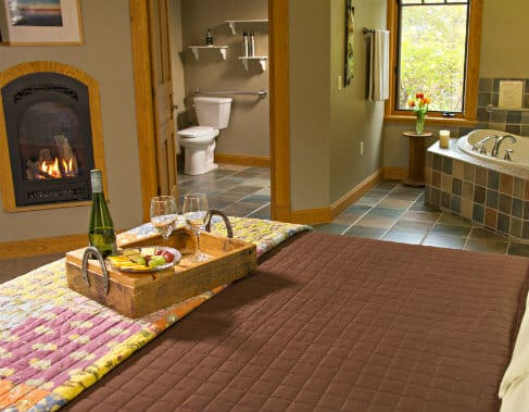 Tan guest room with fireplace, bed topped with tray of wine, cheese, crackers and grapes, and view of corner spa tub