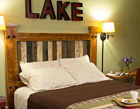 mission style wooden headboard with wood block letters on wall above spelling out the word lake against soft green wall with shaded sconce next to bed covered in neutral brown spread and four pillows with crip white pillow cases.