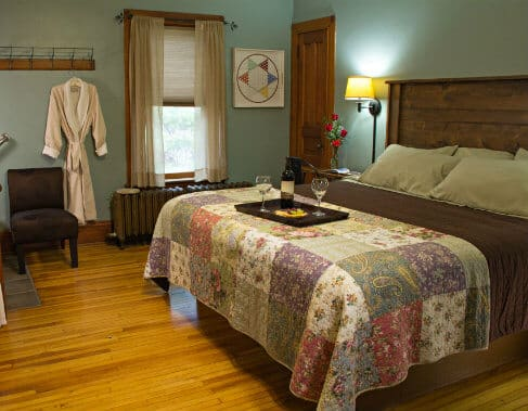 Blue guest room with sloped ceilings and wood floors, wood bed with quilt covering topped with tray of grapes and wine