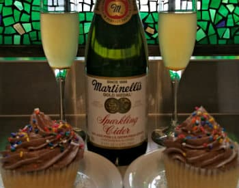 Bottle of sparkling cider, two champagne glasses filled with cider and two chocolate cupcakes with sprinkles