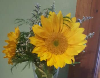 Bright yellow sunflowers and purple wildflowers in a clear glass vase
